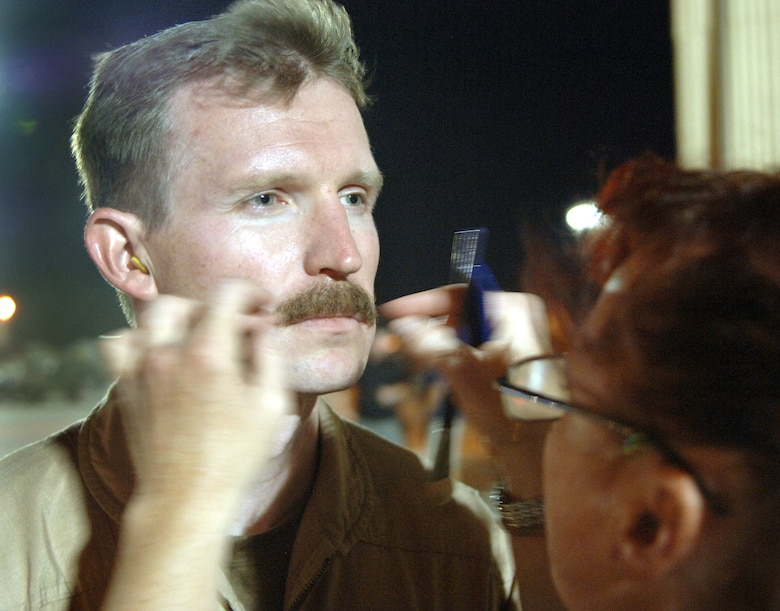 """Makeup artist Robin Beauchesne glues a mustache on Capt. Brian Reece on the set of the movie """"Transformers"""" at Holloman Air Force Base, N.M., on Wednesday,  May 31, 2006. The movie is scheduled for release in June 2007. Captain Reece is with the 58th Special Operations Wing at Kirtland AFB, N.M. (U.S. Air Force photo/Tech. Sgt. Larry A. Simmons)"""