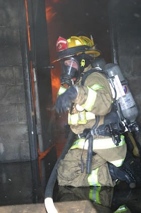 John Torzilli of the Marine Corps Recruit Depot Parris Island Fire and Rescue Department prepares to battle a blaze in the burn building here.  Torzilli is one of many area firefighters who participated in the weeklong fire and rescue training here.