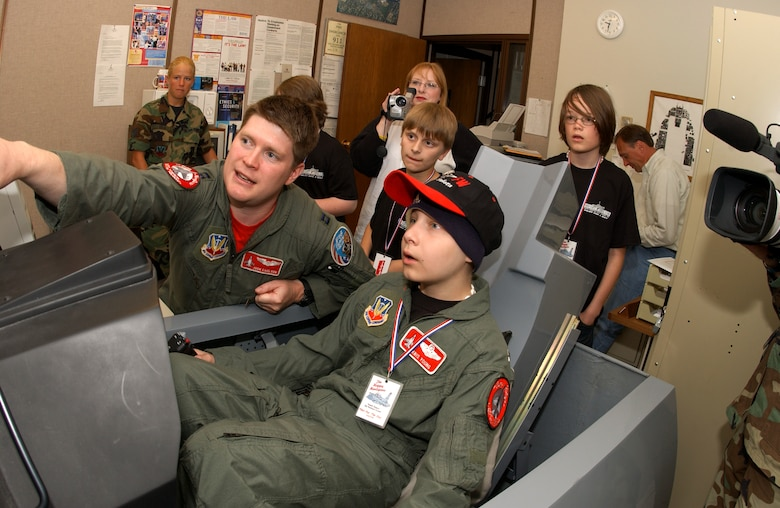 """Capt. Joshua Carlson helps """"pilot for a day"""" Kris Young operate an F-16 Fighting Falcon flight simulator at the Air National Guard's 119th Fighter Wing in Fargo, N.D., on Friday, June 2, 2006. The pilot for a day program gives children with serious health conditions a day away from medical tests and treatments. Thirteen-year-old Kris, from West Fargo, N.D., has Burkitt's lymphoma, a type of cancer. He has two uncles in the Air Force, one in the Marines, one in the Coast Guard and one in the Army. Captain Carlson is with the 178th Fighter Squadron. (U.S. Air Force photo/Senior Master Sgt. David H. Lipp)"""