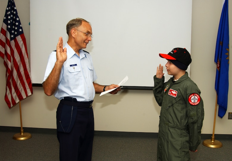 """Col. Patrick Martin swears in Kris Young as a """"pilot for a day"""" at the Air National Guard's 119th Fighter Wing in Fargo, N.D., on Friday, June 2, 2006. The pilot for a day program gives children with serious health conditions a day away from medical tests and treatments. Thirteen-year-old Kris, from West Fargo, N.D., has Burkitt's lymphoma, a type of cancer. He has two uncles in the Air Force, one in the Marines, one in the Coast Guard and one in the Army. Colonel Martin is vice commander of the 119th FW. (U.S. Air Force photo/Senior Master Sgt. David H. Lipp)"""