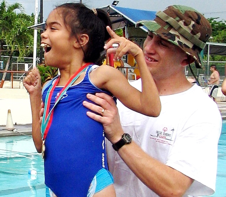 Staff Sgt. Michael Cole assists gold-medal winner Desirae Tyquiengco during the 2006 Guam Special Olympics aquatic event on Saturday, June 3, 2006. Volunteers from the 393rd Expeditionary Bomb Squadron and 36th Expeditionary Aircraft Maintenance Squadron at Andersen Air Force Base, Guam, assisted during the events, acting as official timekeepers, distributing medals and helping in other areas. Sergeant Cole is assigned to the 393rd EBS. (U.S. Air Force photo/Tech. Sgt. Mikal Canfield)