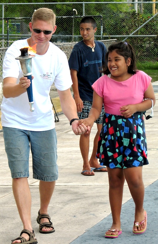 Capt. Ryan Huckabay holds the hand of athlete Miah Meneses while carrying the torch at the opening ceremonies of the 2006 Guam Special Olympics aquatic event on Saturday, June 3, 2006. Volunteers from the 393rd Expeditionary Bomb Squadron and 36th Expeditionary Aircraft Maintenance Squadron at Andersen Air Force Base, Guam, assisted at the events, acting as official timekeepers, distributing medals and helping in other areas. Captain Huckabay is assigned to the 393rd EBS. (U.S. Air Force photo/Tech. Sgt. Mikal Canfield)