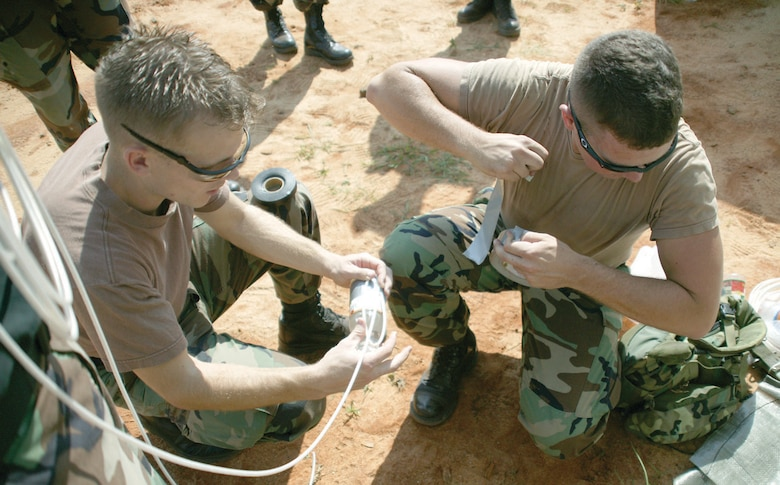 20th Civil Engineer Squadron explosive ordnance disposal technicians, Senior Airmen Ken Schnorbus and Steve Conrad, prepare an explosive charge using detonating cord to disrupt the improvised explosive device.  (U.S. Air Force Photo/Senior Airmen John Gordinier)