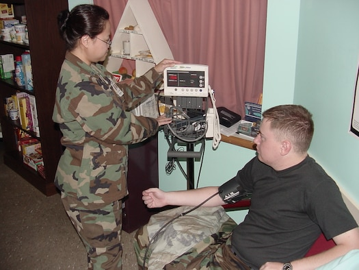 First Lt. Luzviminda Molina, 60th Medical Operations Squadron clinical nurse, checks the blood pressure of Airman 1st Class Joseph Burnell, 573rd Global Support Squadron, during a recent HOLDSS class. (U.S. Air Force photo/Jim Spellman)
