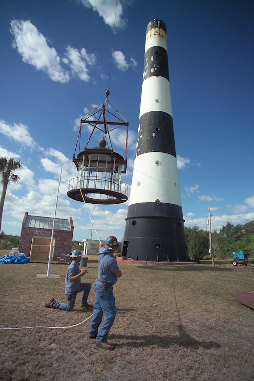 CAPE CANAVERAL AIR FORCE STATION, Fla.—Construction workers guide the 18,000-pound roof and lamp room to the ground from atop the 151-foot Cape Canaveral Lighthouse. The structures were removed as part of an ongoing renovation project. This is the first time the original lamp room has been separated from the lighthouse base in more than 100 years.