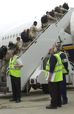 Passenger service personnel from the 727th Air Mobility Squadron passenger terminal at RAF Mildenhall, wearing fluorescent jackets, direct members of the 48th Security Forces Squadron to safely board an aircraft June 2. In addition to working with deploying members, the passenger service agents also work with travellers flying space-available, and on commercial rotators. (U.S. Air Force photo by Karen Abeyasekere)