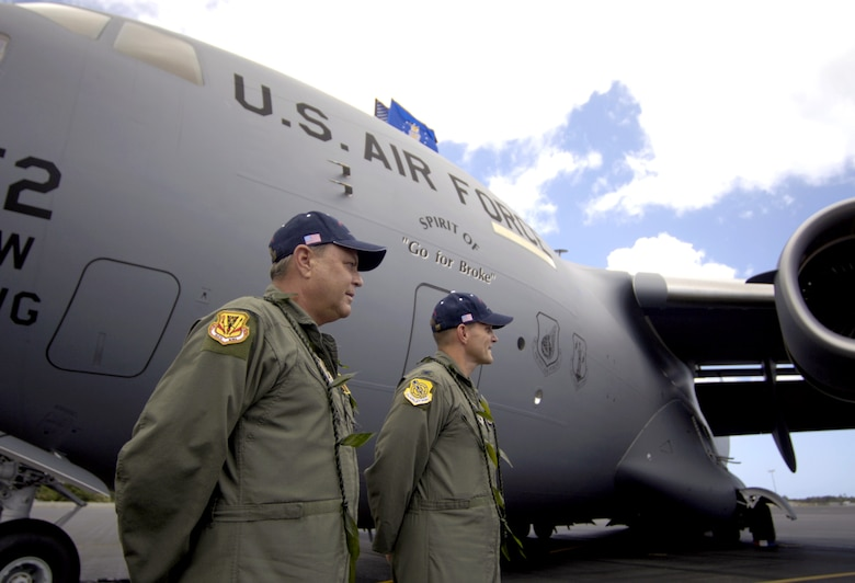 """Brig. Gen. Peter S. Pauling and Col. William Changose listen to the blessing of a C-17 Globemaster III during its arrival ceremony at Hickam Air Force Base, Hawaii, on Wednesday, June 14. The aircraft """"Spirit of 'Go for Broke'"""" is named in honor of the 442nd Regimental Combat Team. General Pauling is commander of the Hawaii Air National Guard's 154th Wing. Colonel Changose is the 15th Airlift Wing commander. (U.S. Air Force photo/Tech. Sgt. Shane A. Cuomo)"""