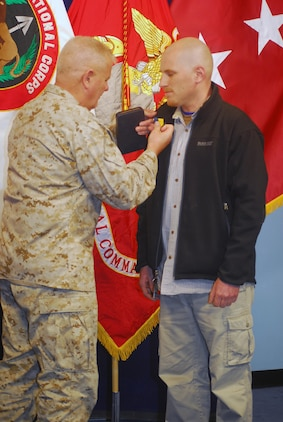 Maj. Gen. Paul Lefebvre, deputy commanding general, Multi-National Corps - Iraq, awards cameraman Chris Jackson with the Department of the Navy Distinguished Public Service Award Jan. 24 at Al Faw Palace for pulling Sgt. Courtney Rauch from a burning humvee in Afghanistan Aug. 3, 2008.