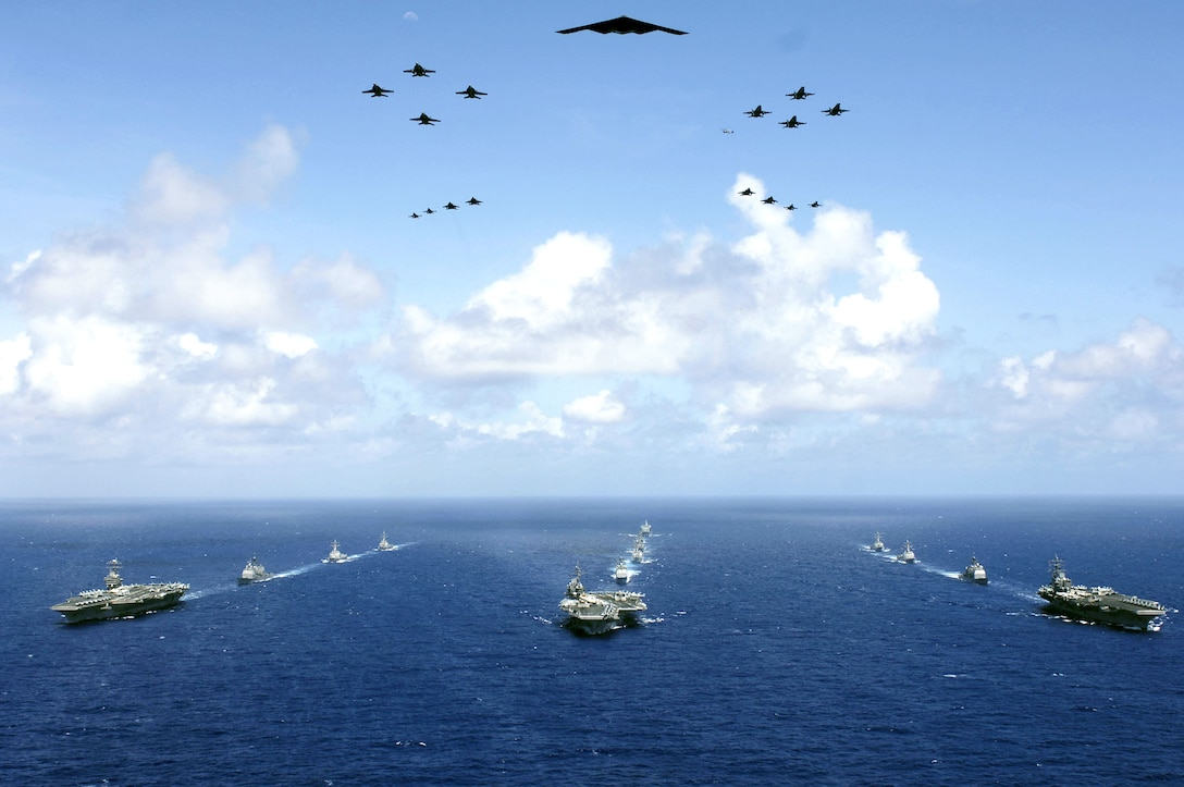 A B-2 Spirit and 16 other aircraft from the Air Force, Navy and Marine Corps fly over the USS Kitty Hawk, USS Ronald Reagan and USS Abraham Lincoln carrier strike groups in the western Pacific Ocean on Sunday, June 18, to kick off Exercise Valiant Shield 2006. The joint exercise consists of 28 naval vessels, more than 300 aircraft and approximately 20,000 servicemembers. (DOD photo/Photographer's Mate 3rd Class Jarod Hodge)
