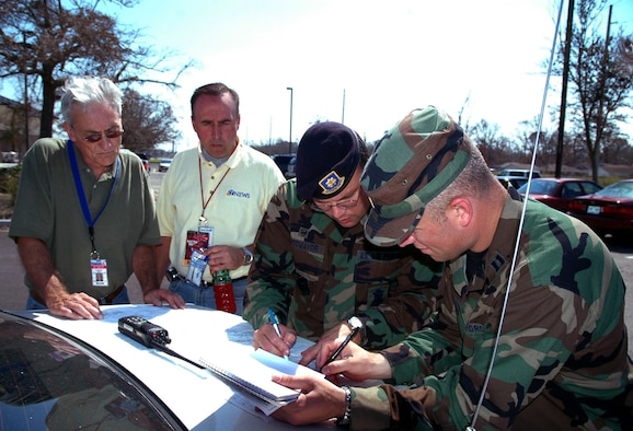 KEESLER AFB, Miss. – Maj. Alexis Sotomayor, 81st Security Forces Squadron commander here, (second from right) goes over map of the base Sept. 5 with Capt. Warren Neary, 90th Space Wing chief of Public Affairs (right), and embedded media members Scott Wright, NBC 9 News KUSA cameraman (left), and Tony Kovaleski, ABC 7 News KMGH reporter. Air Force Space Command embedded media with its units to cover helicopter and security forces support for the JTF Katrina relief effort. (Courtesy photo)