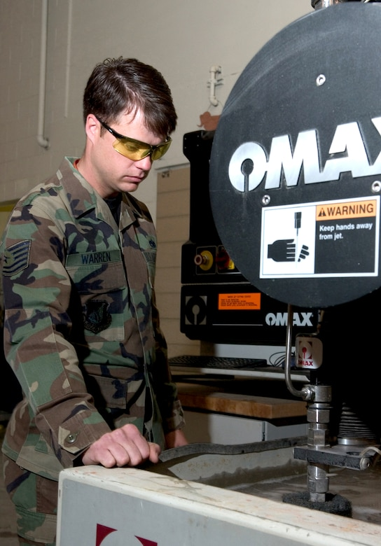 Tech. Sgt. Albern Warren checks on the progress of an abrasive water-jet cutter while cutting metal for an aircraft part on Friday, June 16. Sergeant Warren is assigned to the 3rd Equipment Maintenance Squadron metals technology shop at Elmendorf Air Force Base, Alaska. (U.S. Air Force photo/Staff Sgt. Alan Port)