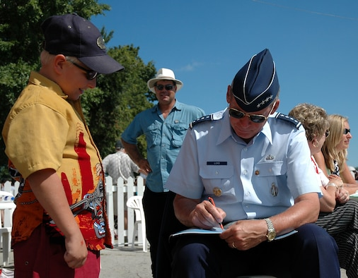 """TORONTO – General Lance W. Lord, Air Force Space Command commander, signs an autograph for an aspiring pilot at the Canadian International Air Show here Sept. 4. The general opened the show with a salute to veterans on """"U.S. Air Force Day."""""""