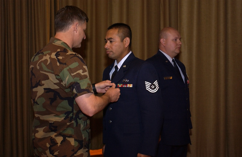 Tech. Sgt. Tyrone Sevening receives the Bronze Star Medal from Col. Michael Bartley, 99th Air Base Wing commander, Monday during commander's call in the base theater at Nellis Air Force Base, Nev. Tech. Sgt. Andrew Morin (right) also received the Bronze Star. Both NCOs, assigned to the 99th Logistics Readiness Squadron, were convoy commanders in Iraq. (U.S. Air Force photo/Staff Sgt. Colette Bennett)