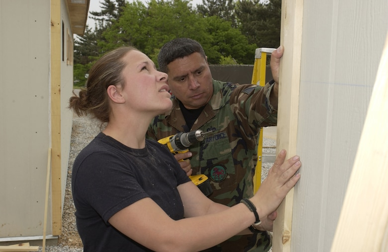 KUNSAN AIR BASE, Republic of Korea – Tech. Sgt. Paul Cucchiaran (right), 555th RED HORSE Squadron, Nellis AFB, Nev., and Staff Sgt. Jonnie Jordan, 307th RHS Barksdale AFB, La., place corner trim on a new SEA hut at Wolf Pack Park in May. The $320,000 project replaced the usual tents constructed by deployed personnel and allows for additional electricity, air conditioning and lighting. (Air Force photo by Tech. Sgt. Demetrius Lester)