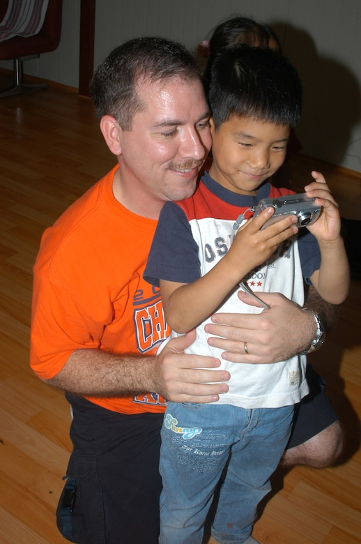 KUNSAN AIR BASE, Republic of Korea -- Master Sgt. Jeff Stokes saves a few memories while posing with a Korean boy after English class. (Air Force photo by Staff Sgt. Becky Nelson)