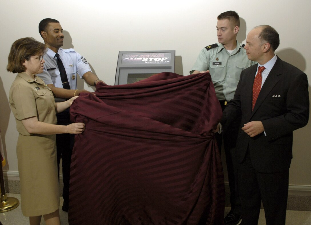 (From left) Navy Chief Petty Officer Jana Perez, Tech. Sgt. Timothy Gerald and Army Staff Sgt. Lonny Sharp unveil the new Joint Services OneStop Kiosk at the Pentagon on Thursday, June 29, with John Vonglis, principal deputy assistant secretary of the Air Force for financial management. (U.S. Air Force photo/Tech. Sgt. Cohen A. Young)