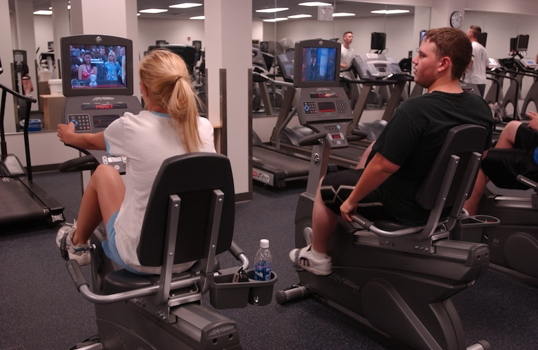 MINOT AIR FORCE BASE, N.D. -- Heather Thompson and  Michael Patterson ride stationary bikes while watching TV at the McAdoo Sports and Fitness  Center June 28, 2006. Most of the center's new cardio equipment comes with its own TV.  The newly renovated center cost more than $9.5 milion and took more than 18 months to complete. (photo by Airman 1st Class Joe Rivera)