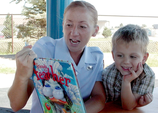 BUCKLEY AFB, Colo. – Airman 1st Class Randi Miles, 460th Comptroller Squadron debt manager, reads to Keenan Wade and other children at the Child Development Center here. Each Thursday morning since early May, volunteers from the 460th Comptroller Squadron have been donating 30 minutes of their time to bring books to life and encourage literacy at the Child Development Center here. (Photo by 1st Lt. Caroline Wellman)