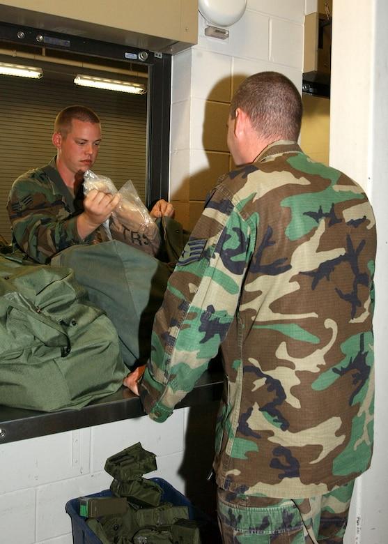 Senior Airman Jon Reed, 16th Civil Engineer Squadron, checks the contents of his A-bag.