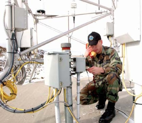 MINOT AIR FORCE BASE, N.D. -- Senior Airman Matthew Rohler, 5th Communication Squadron, checks for a dial tone between the Remote Automated Weather Station and the 5th Operations Support Squadrons Weather Flight at Alpha 01. The RAWS is a new state-of-the-art weather system that detects real time visibility, temperature, humidity and many other weather factors.
