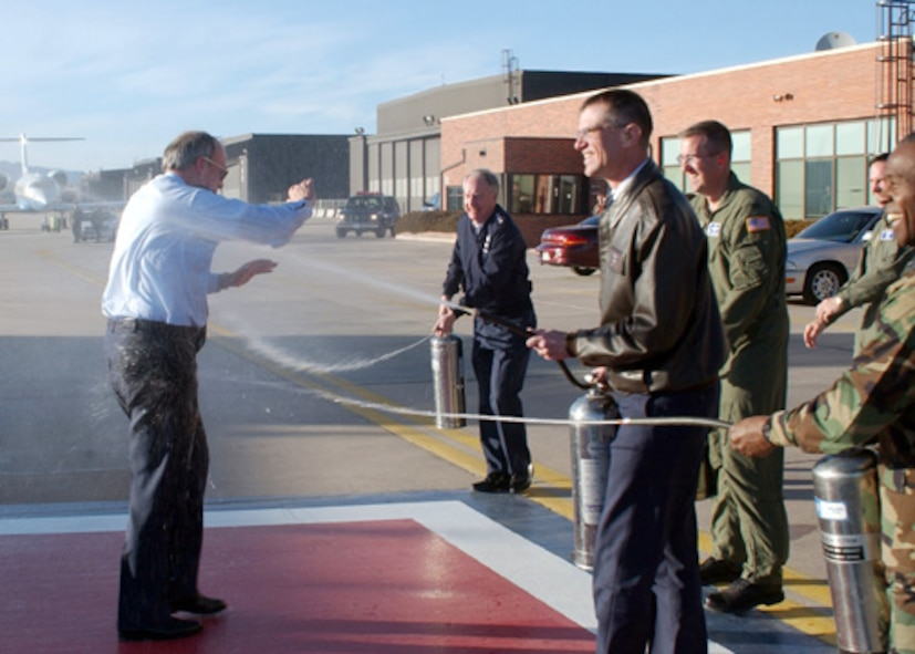 """PETERSON AIR FORCE BASE, Colo. -- Lt. Gen. Frank Klotz, Col. Jay Santee, Col. John Hyten, and Col. Jimmy McMillian hose down General Lance W. Lord, Air Force Space Command commander, after his """"Fini Flight"""" here Feb. 27. The Fini Flight is an Air Force tradition of dousing an Airman after his or her final flight with the unit. General Klotz is AFSPC vice commander, Colonel Santee is the 21st Space Wing commander, Colonel Hyten is the 50th Space Wing commander, and Colonel McMillian is the AFSPC commander's executive officer."""