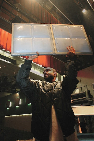 CANNON AIR FORCE BASE, N.M. -- Airman Wardell Wheeler Jr., 27th Services Squadron, pulls down light panels after the Top In Blue show Feb. 16. (U.S. Air Force photo by Janet Taylor-Birkey)