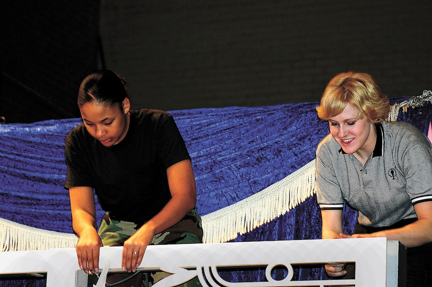 Senior Airman Shawnta Butler, 27th Operation Support Squadron, helps Staff Sgt. Amanda Young, Lackland Air Force Base, build the railing for the upper stage. (U.S. Air Force photo by Janet Taylor-Birkey)
