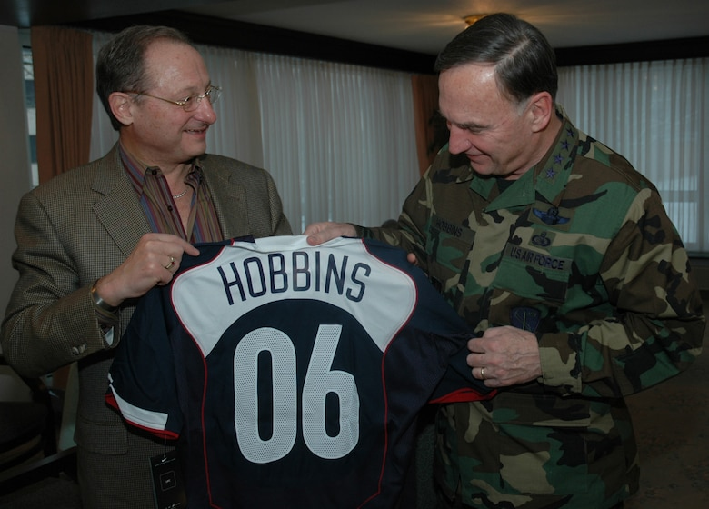 RAMSTEIN AIR BASE, Germany (USAFENS) -- Dr. S. Robert Contiguglia, President of the U.S. Soccer Federation (left), presents Gen. Tom Hobbins, U.S. Air Forces in Europe commander, with an honorary team jersey here Feb. 28. The U.S. Men's Soccer Team is staying on base prior to playing against Poland Mar. 1. (Photo by 1st Lt. Elizabeth Culbertson)