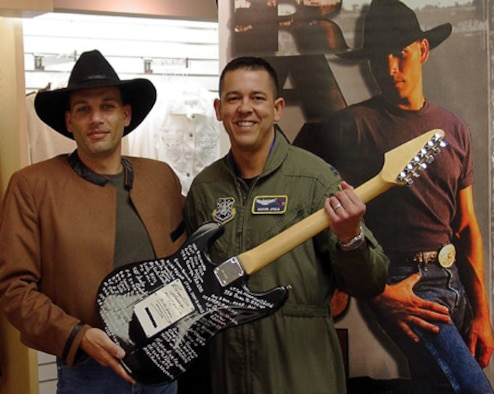 "ONIZUKA AIR FORCE STATION, Calif. — Capt. Manuel Ayala, with the 21st Space Operations Squadron here, recently signed ""America's Guitar"" at the Moffett Federal Airfield Navy Exchange in Sunnyvale, Calif. The guitar came to Moffett Airfield via country music artist Raymond Harris, who is touring military installations and collecting signatures on the guitar from members of the armed forces and their families. Each military installation Mr. Harris visits will have a guitar named after it."