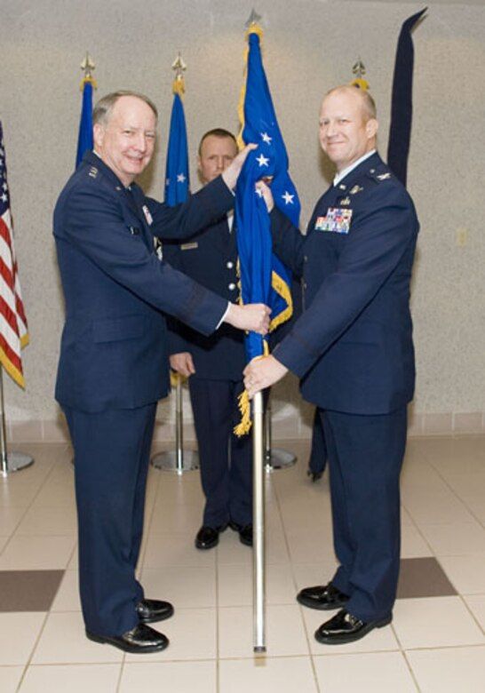 SCHRIEVER AIR FORCE BASE, Colo. -- Lt. Gen. Frank Klotz, Vice Commander, Air Force Space Command, presents the new flag for the renamed Space Innovation and Development Center to its commander, Col. Larry Chodzko. The center was formerly called the Space Warfare Center.