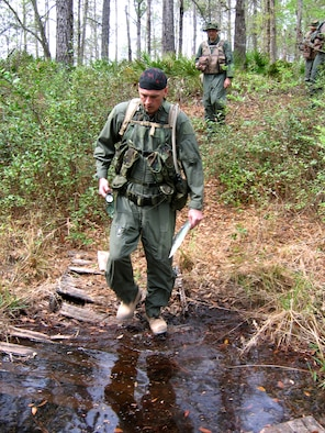 MOODY AIR FORCE BASE, Ga. - Master Sgt. John Buckler, 41st Rescue Squadron, and Capt. Joseph Booth, 347th Operations Support Squadron, cross a stream during combat survival training March 14 at Grand Bay Wildlife Management Area here. Six Moody aircrew members completed the refresher training, which teaches survival skills in combat and peacetime situations. (Photo by Airman Eric Schloeffel)