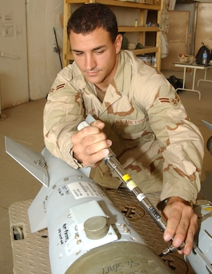 Airman 1st Class Michael Claypoole, a munitions systems journeyman with the 332nd Expeditionary Maintenance Squadron, torques down the tail fin assembly of a 500-pound Joint Direct Attack Munition after it was delivered to Balad Air Base in 2004. (Air Force photo by Master Sgt. David Reagan)