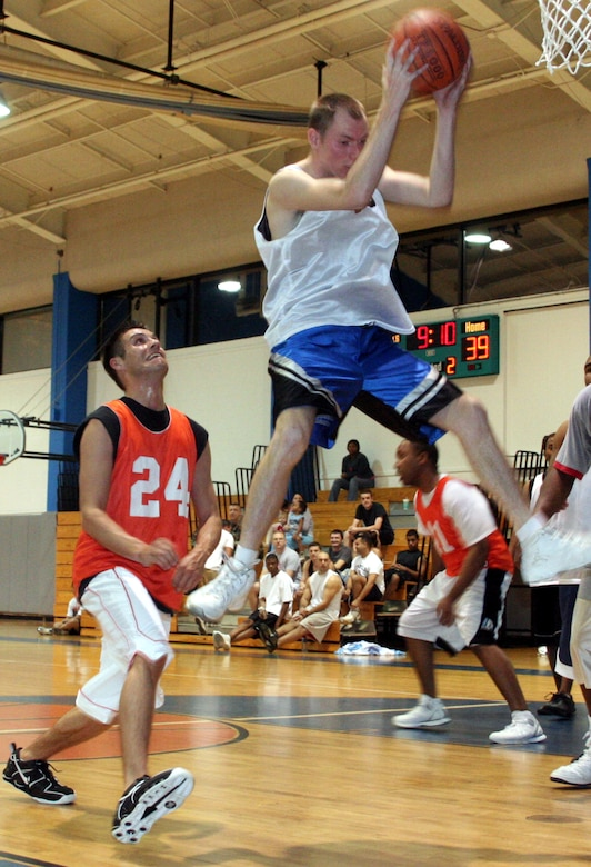 Jeff White, 16th Equipment Maintenance Squadron, rips down a defensive rebound in front of Lee Elamn, 16th Security Forces Squadron Wednesday night.  EMS won the first game of the 2006 intramural basketball playoffs with a 57-48 jailing of SFS.