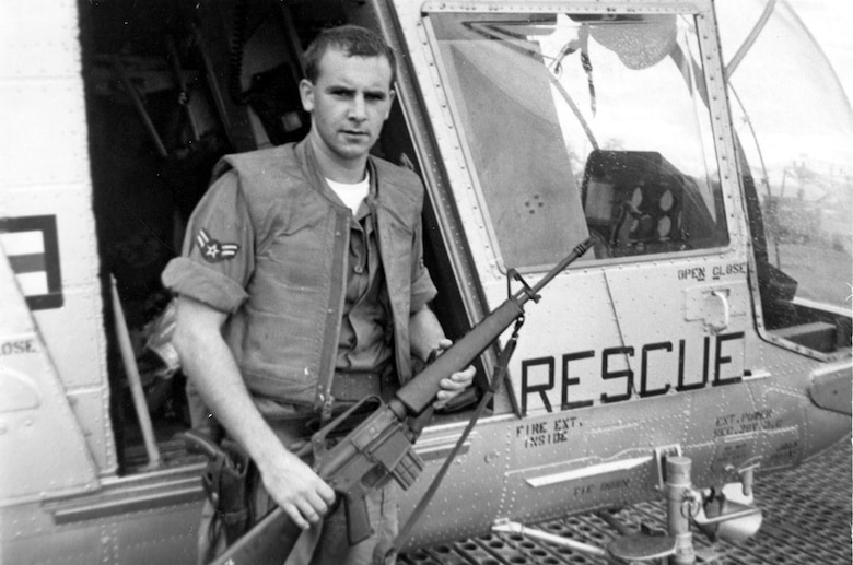 A1C William Pitsenbarger with an M-16 outside the HH-43. (U.S. Air Force photo)