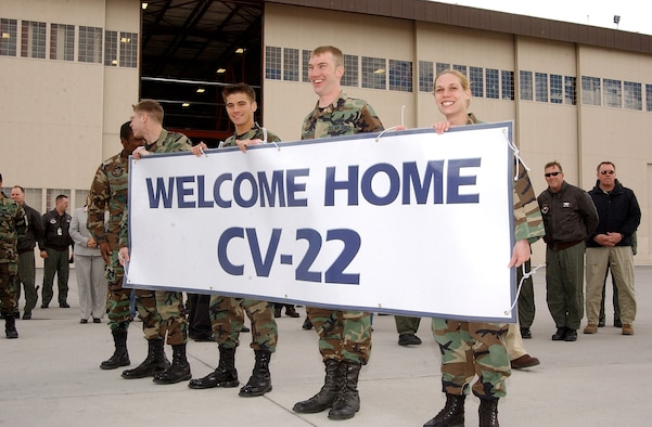 Airmen with the 58th Special Operations Wing hold a banner welcoming the Air Force's first operational CV-22 Osprey to Kirtland AFB, N.M., Monday, March 20, 2006.  The aircraft was flown to Kirtland by Lt. Gen. Michael W. Wooley, commander of Air Force Special Operations Command. (U.S. Air Force photo/Staff Sgt. Markus Maier)