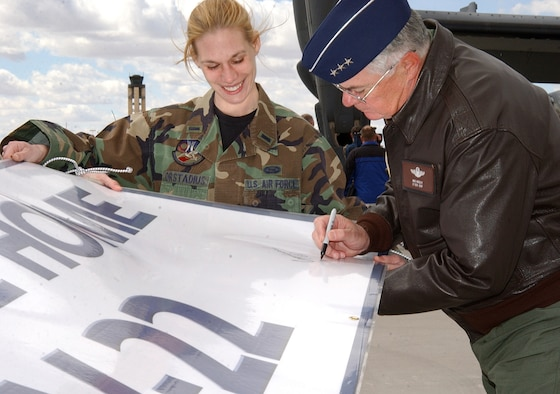 1st Lt. Anna Orstadius steadies a welcome banner while Lt. Gen. Mike Wooley, autographs it at Kirtland Air Force Base, N.M, after the first CV-22 Osprey arrived at the base Monday, March 20, 2006. General Wooley is commander of Air Force Special Operations Command. Lieutenant Orstadius is with the 58th Operational Support Squadron. (U.S. Air Force photo/Staff Sgt. Markus Maier)