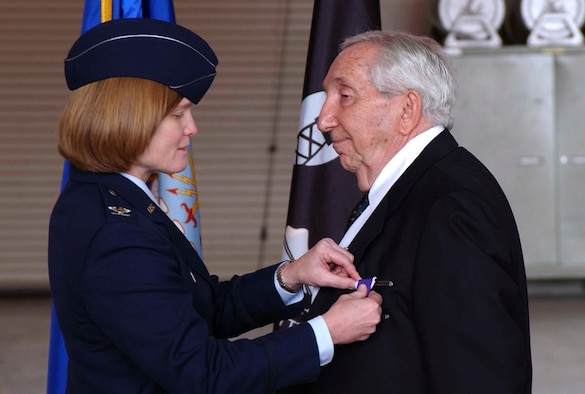 Col. Lyn Sherlock, commander of the 60th Air Mobility Wing, pins the Purple Heart Medal on Mr. Leo Bach.  He received five other medals during the ceremony, including the WWII victory medal and the Prisoner of War Medal. (U.S. Air Force photo by Nan Wylie)
