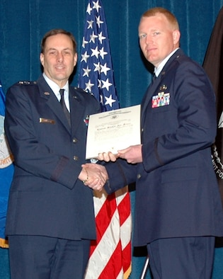 Maj. Gen. Craig E. Campbell (left) presents 2nd Lt. Michael Maule his Certificate upon completion of the Academy of Military Science's six-week commission course. Maule also received the Class Speaker Award. Campbell is the Adjutant General for the State of Alaska, commander of the Alaska National Guard and the Commissioner of the Department of Military and Veterans Affairs.