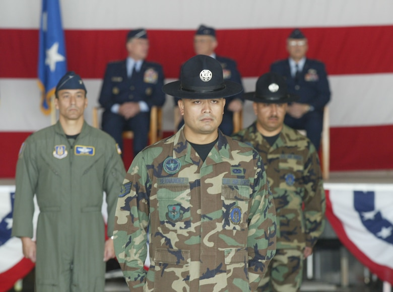 From the left, Col. Mike Kim, vice commander of 22nd Air Force and commander of the troops, along with training instructors from the 37th Training Wing, Lackland Air Force Base, Texas, await the next command for the troop formations at the Change of Command ceremony.