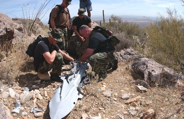 Airmen with the 56th Civil Engineer Squadron explosive ordnance disposal unit and the 56th Equipment Maintenance Squadron at Luke Air Force Base, Ariz., examine an F-16 Fighting Falcon triple ejector rack in the White Tank Mountains on Thursday, March 23, 2006. The Airmen were ensuring the rack didn't contain unexploded cartridges. The rack was released from a 61st Fighter Squadron F-16 during an in-flight emergency on Aug. 11, 2003.  A local resident found the item while hiking and led the Air Force team to the site. (U.S. Air Force photo/Tech. Sgt. Angela Clemens)