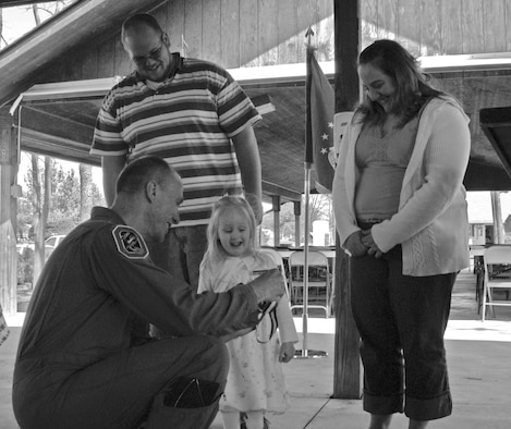 Col. Mike Roberts, Ohio Air National Guard's 178th Fighter Wing vice commander, presents Elizabeth Koerner, 3, with a Young Heroes Medal of Honor as her parents, Matthew and Hannah Koerner, look on. (Air Force photo by 2nd Lt. Holly Layer)