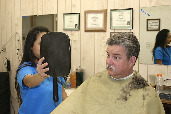 CANNON AIR FORCE BASE, N.M. - Sam Irons, 27th Comptroller Squadron, checks his new look after a haircut Monday. After retiring from the Air Force two years ago, Mr. Irons grew his hair for a special cause — Locks of Love. (U.S. Air Force photo by Janet Taylor-Birkey)