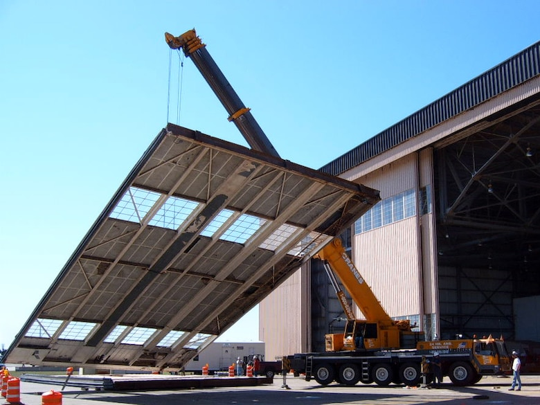 A crane lowers one of the original Eason Hangar doors to the ground as part of phase 1 repairs.  The hangar was built in 1957 and was heavily damaged from recent hurricanes.  All 16 doors will be replaced by the end of the year along with other modifications.