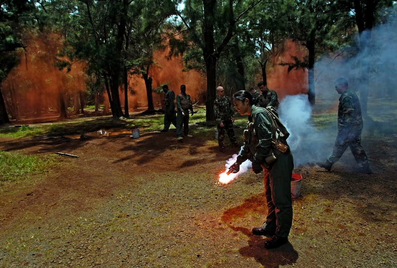 Students practice igniting survival flares during a ground survival refresher course at Schofield Barracks, Hawaii, on Thursday, May 4, 2006. The course provides realistic training for aircrew members and concentrates on the principles, techniques and skills necessary to survive in any environment. (U.S. Air Force photo/Tech. Sgt. Shane A. Cuomo)