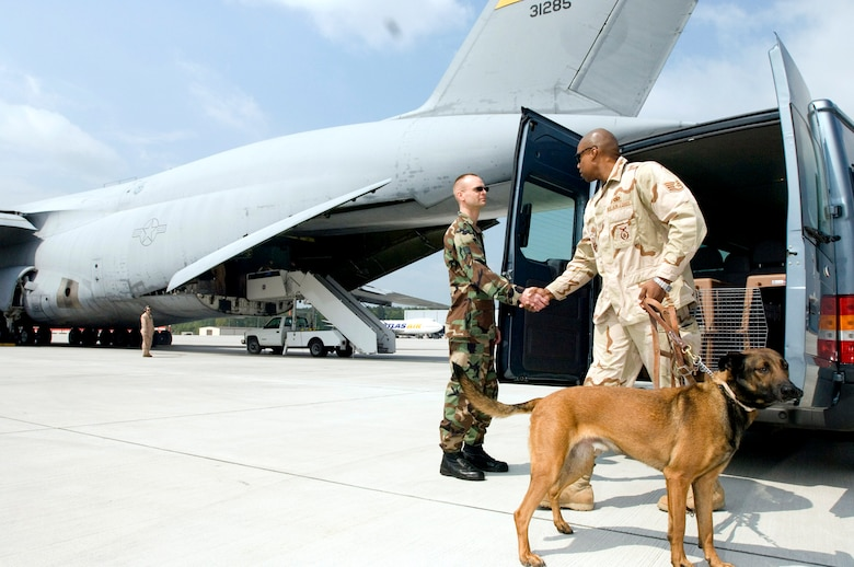 Staff Sgt. Robert Van Hulle (left) says goodbye as Staff Sgt. Markus Hunt and his military working dog, Diego, prepare to board an aircraft at Ramstein Air Base, Germany, on Tuesday, May 9, 2006. Sergeant Van Hulle is the 435th Security Forces Squadron military dog handler liaison. Sergeant Hunt and Diego were returning to Misawa Air Base, Japan, after a six-month tour supporting Operation Iraqi Freedom. (U.S. Air Force photo/Master Sgt. John E. Lasky)