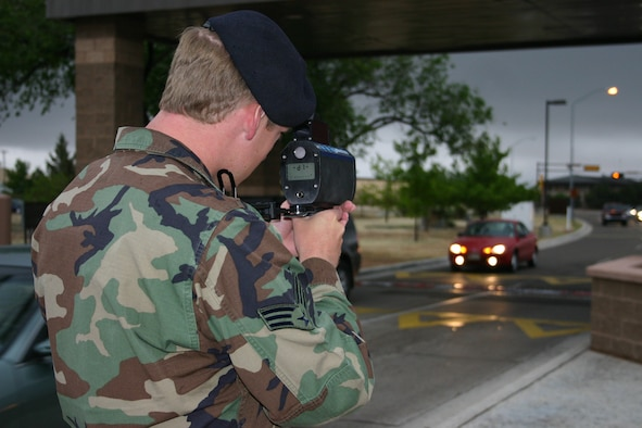 CANNON AIR FORCE BASE, N.M. --  Senior Airman William Nobel, 27th Security Forces,Squadron gets ready to clock a vehicle's speed leaving the main gate at Cannon May 5. Drivers will notice an increased presence at the gates because of speeding vehicles, said Tech. Sgt. Rich Jones, 27th SFS. Vehicles speeding out the gate faster than the posted 5 mph causes damage to the pop-up barriers. Speeding tickets will cost active duty personnel at least three points. Non active duty individuals will be fined $15 for speeding one to 10 miles per hour over the posted speed limit. Sergeant Jones said plans are under way to install speed bumps to further deter speeding drivers. (U.S. Air Force photo by Greg Allen)