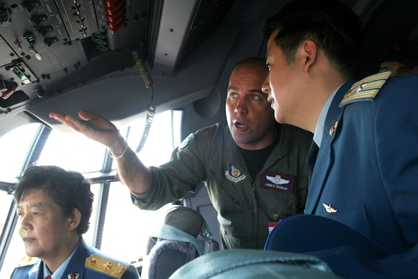 Maj. James Dignan describes some of the features of the C-130J Hercules to Chinese Maj. Gen. Yue Xicui (left) and Maj. Zhang Dezhao on May 16, 2006 at the Berlin Air Show.  General Xicui is the Chinese Air Force's first female pilot and has more than 6,000 flying hours.  Various models of U.S. military aircraft and about 60 support personnel from bases in Europe and the United States are attending the air show at Berlin-Schoenefeld Airport May 16-21.  Major Dignan is a pilot with the 403rd Wing, Keesler Air Force Base, Miss.  (U.S. Air Force photo/Maj. Pamela A.Q. Cook)