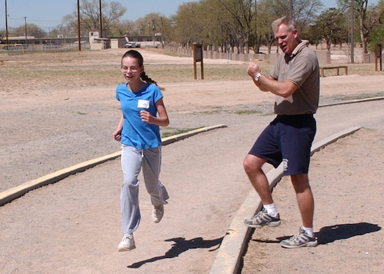 KIRTLAND AIR FORCE BASE, N.M. - Tech. Sgt. Matt Moore of Kirtland's NCO Academy, cheers Megan Norris along during her mile run. Megan ran the fastest girl's time at the event in approximately 7 minutes. (Air Force photo by Dennis Carlson)