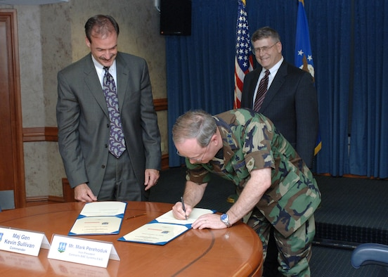 HILL AIR FORCE BASE, Utah - Maj. Gen. Kevin Sullivan, Ogden Air Logistics Center commander, signs the BAE Systems partnership agreement May 11 at Hill Air Force, Base Utah. At left, Mark Perehoduk, vice president for contracts at BAE Systems, awaits his turn to sign the document. In back is BAE Systems Jeff Cook, vice president for readiness and sustainment. (Air Force photo by Carl Burnett)