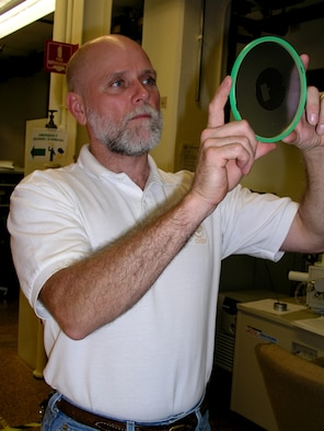 WRIGHT-PATTERSON AIR FORCE BASE, Ohio -Dr. James Scofield of the Air Force Research Laboratory Propulsion Directorate's Electrical Technology and Plasma Physics Branch inspects a Schottky diode.  He received the 2006 Federal Laboratory Consortium Award for Excellence in Technology Transfer for pioneering the new and improved silicon carbide (SiC) Schottky diodes.  (Air Force photo)